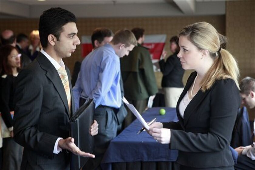 Mahesh Sahni, of Worcester, Mass., left, holds his resume while speaking with Laura Erickson, of Boston, right, a recruiter for Prudential at the BostonHires job fair at a hotel in Boston, Tuesday, Feb. 2, 2010. The number of newly laid-off workers filing initial claims for jobless benefits rose unexpectedly last week, evidence that layoffs are continuing and jobs remain scarce.(AP Photo/Steven Senne)