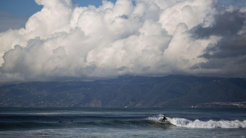 EL SEGUNDO, CALIF. - JANUARY 12: A surfer catches a wave as clouds hang over the Santa Monica mounta