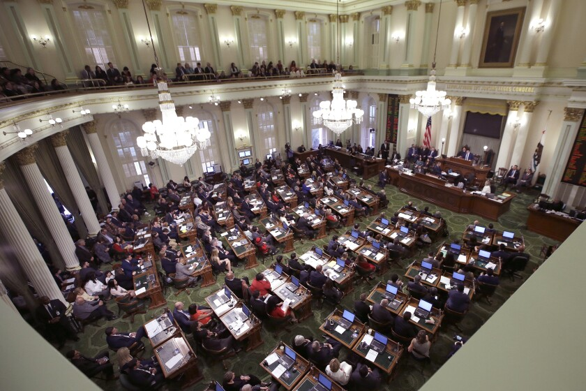 FILE - Members of the state Assembly listen to an address by Assembly Speaker Anthony Rendon, D-Paramount, at the Capitol in Sacramento, Calif., Monday, Dec. 5, 2016. On Monday, Aug. 3, 2020, the California Assembly voted 48-10 to approve a new rule allowing lawmakers at high risk for the coronavirus to vote on bills without being present in the chamber. The vote comes despite an opinion from the Legislative Counsel Bureau saying it likely violates the state Constitution. (AP Photo/Rich Pedroncelli, File)