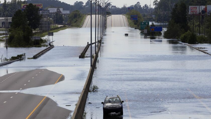 Flooded vehicles sit on a closed section of Interstate 95 in Lumberton, N.C., Monday, Sept. 17, 2018