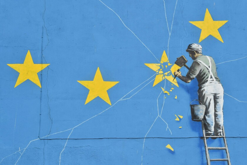 A mural by British artist Banksy depicts a workman chipping away at one of the stars on a European Union flag in Dover, England.
