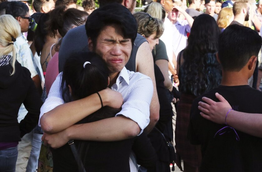 People hug outside Kamiak High School in Mukilteo, Wash., during a vigil for those who were slain Saturday, July 30, 2016. A shooting at a house party has left three people dead and another hurt in the Seattle suburb on Saturday. State troopers arrested the fleeing 19-year-old suspect three countie