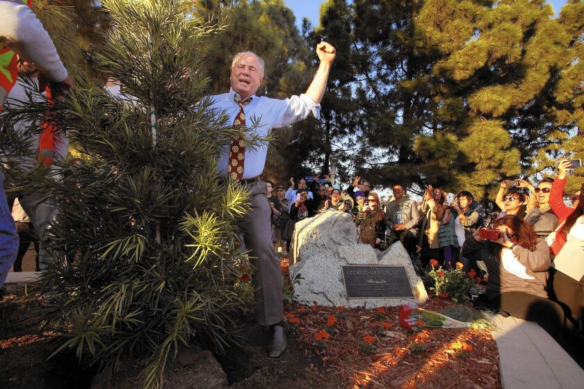 Los Angeles City Councilman Tom LaBonge, center, exults after helping replant the George Harrison Tree in Griffith Park. The original tree, planted a year after Harrison's death in 2001, was destroyed by beetles.
