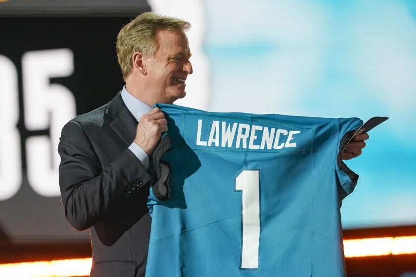 Roger Goodell, comisionado de la NFL, sostiene un jersey con el apellido de Trevor Lawrence,