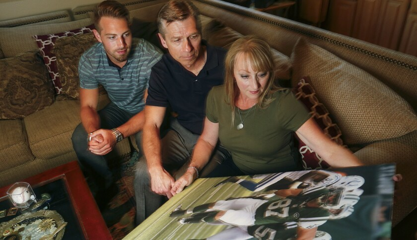 With their youngest son Austin, left, Ralf and Mary Reuland look at a photo of their oldest son, Kon