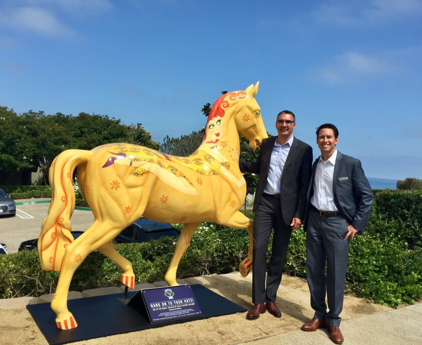 """TextEditor """"Buttercup,"""" an artistic horse was recently installed at L 'Auberge Del Mar as part of the Breeders' Cup """"Art of the Horse"""" program. Standing with Buttercup are Terry Buchholz, general manager of L'Auberge Del Mar, and Bob Harter, director of sales and marketing."""