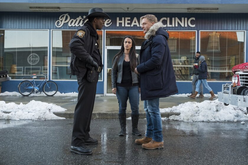 """Corey Reynolds, Sara Tomko and Alan Tudyk stand outside a health clinic in Syfy's """"Resident Alien."""""""