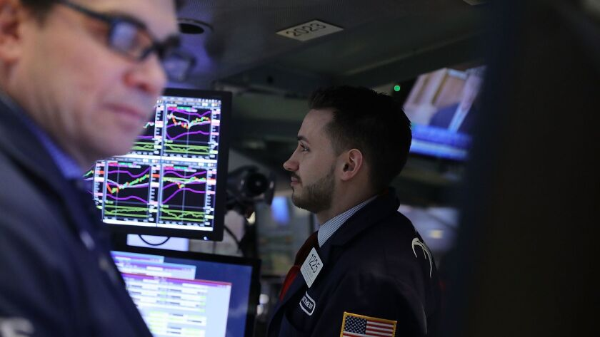 Healthcare and household goods companies fell after Johnson & Johnson and Procter & Gamble gave disappointing quarterly reports. Above, traders work on the floor of the New York Stock Exchange.
