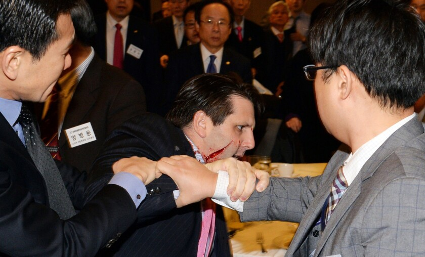 A wounded Mark Lippert leaves the Sejong Cultural Institute in Seoul after a knife attack on March 5.