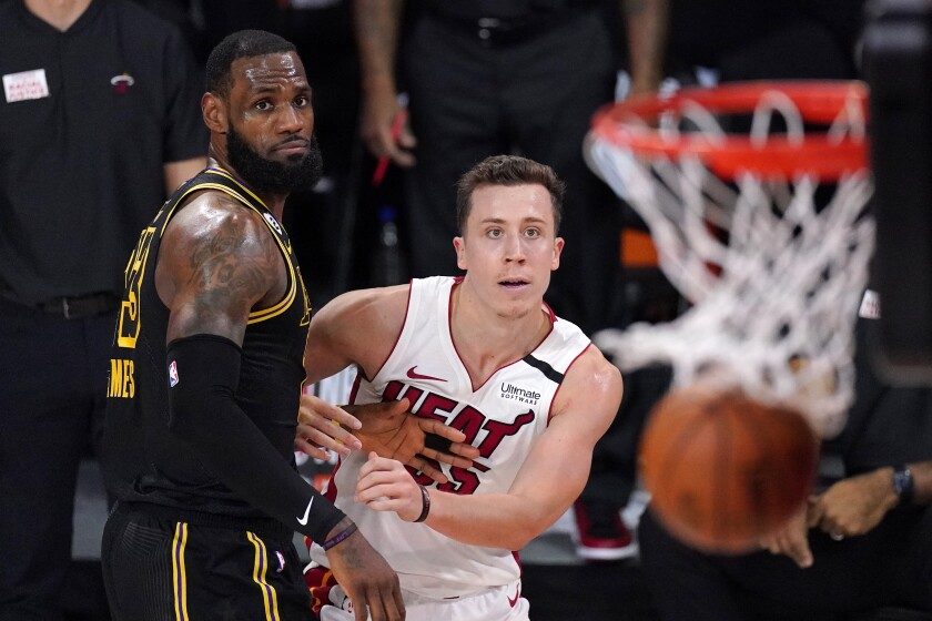 Miami Heat guard Duncan Robinson stands next to Lakers forward LeBron James as he watches a missed shot.