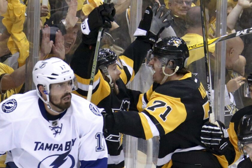 Pittsburgh Penguins' Bryan Rust, center, celebrates with teammate Evgeni Malkin (71) after scoring as Tampa Bay Lightning's Alex Killorn (17) skates away during the second period of Game 7 of the NHL hockey Stanley Cup Eastern Conference finals, Thursday, May 26, 2016, in Pittsburgh. (AP Photo/Gene