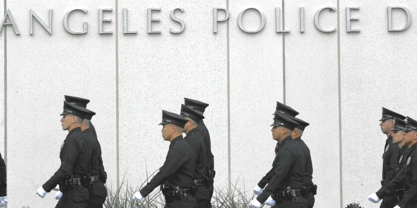 Officers walk in formation in front of LAPD building