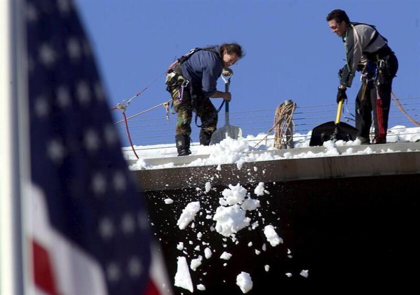 Trabajadores amarrados a líneas de seguridad, remueven nieve del techo del Centro Pepsi en el centro de Denver, luego de una tormenta de nieve, el lunes 11 de abril de 2005. EFE/Archivo