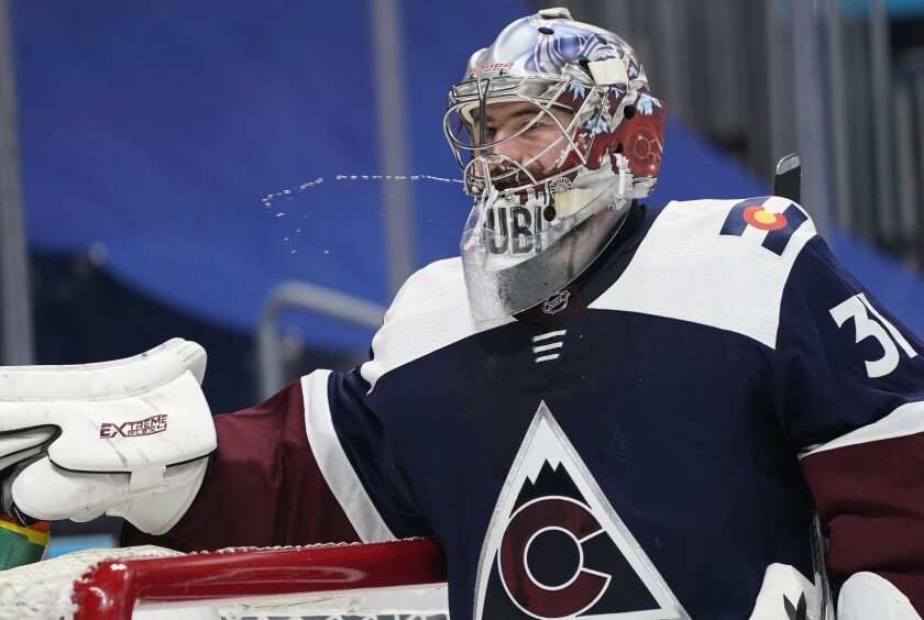 Colorado Avalanche goaltender Philipp Grubauer shoots out a stream of water after taking a drink while waiting for a face off against the Minnesota Wild in the second period of an NHL hockey game Tuesday, Feb. 2, 2021, in Denver. (AP Photo/David Zalubowski)