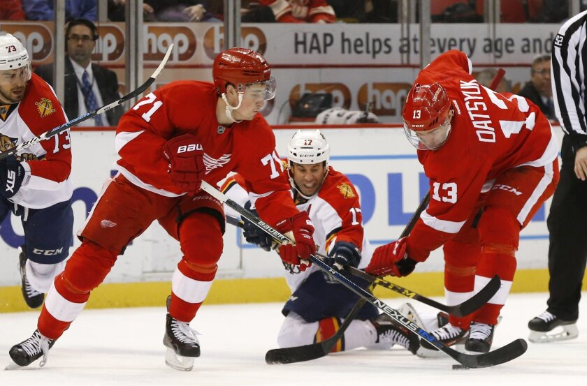 Florida Panthers center Derek MacKenzie (17) battles with Detroit Red Wings center Dylan Larkin (71) and Pavel Datsyuk (13) for the puck in the first period of an NHL hockey game, Monday, Feb. 8, 2016 in Detroit. (AP Photo/Paul Sancya)
