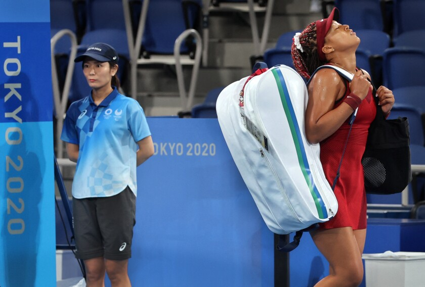 Tennis star Naomi Osaka tilts her head back in frustration while carrying a racket bag