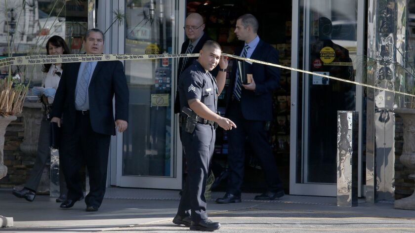 LAPD investigators emerge from the Chevron station mini-mart where a store clerk was shot to death during a robbery in the Los Feliz area.