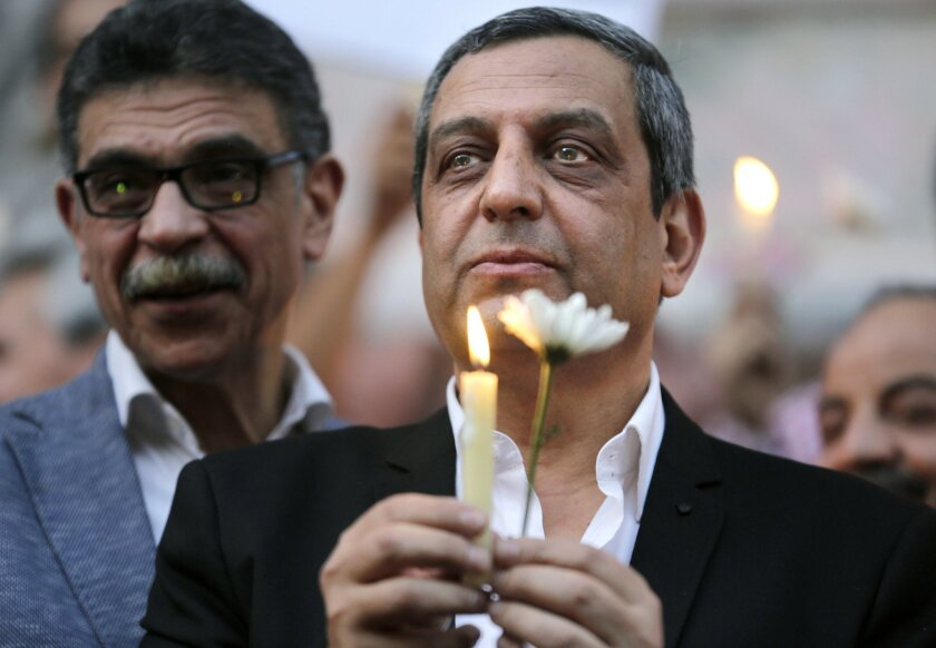 In this Tuesday, May 24, 2016 picture, Yahia Kalash, the head of journalists' union, holds a candle during a candlelight vigil for the victims of EgyptAir flight 804 in front of the Journalists' Syndicate in Cairo, Egypt. The head of Egypt's journalists union and two of its board members have been questioned by prosecutors over allegations that they harbored journalists wanted by authorities and spreading false news, one of the three and their lawyer said on Monday. (AP Photo/Amr Nabil)