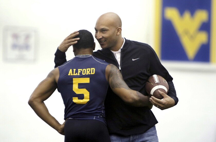 Then-West Virginia assistant coach Lonnie Galloway congratulates wide receiver Mario Alford during the school's NFL pro day in 2015. Louisville has suspended Galloway for the Citrus Bowl.