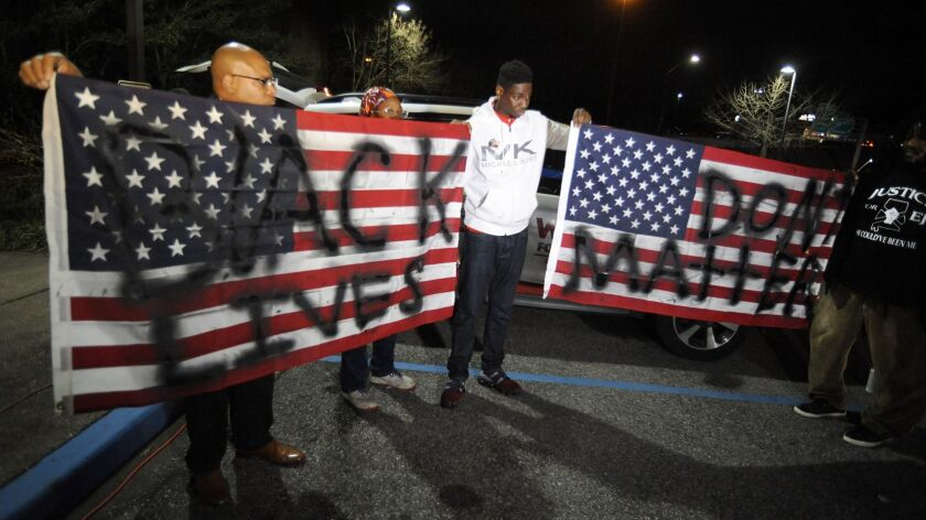 "Activists protesting the police shooting of a black man in an Alabama shopping mall hold U.S. flags painted with the words ""Black lives don't matter"" in Hoover, Ala., on Tuesday."