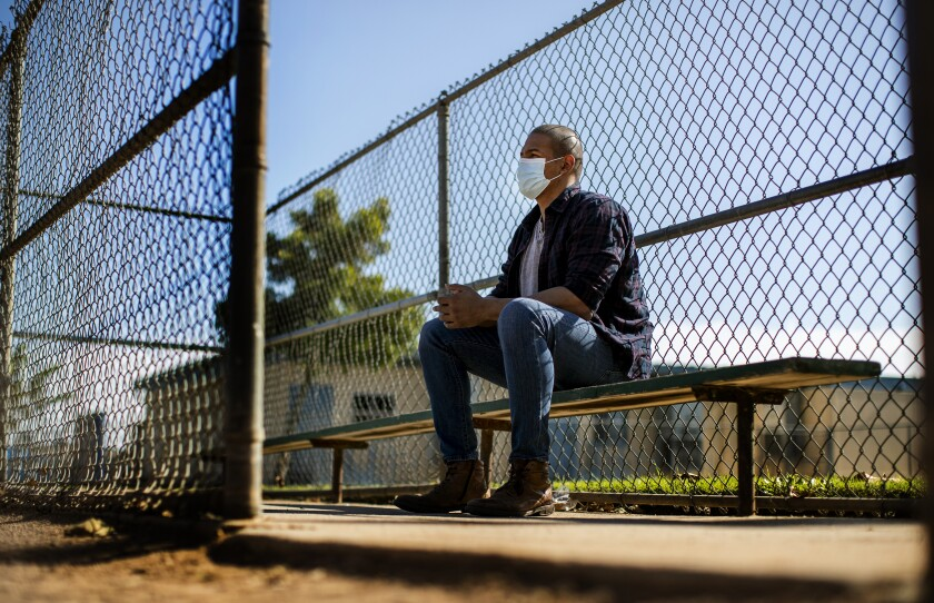 Evie Junior sits on a bench at a baseball diamond near his home in Anaheim