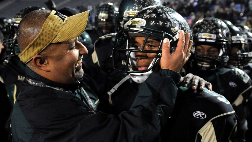 Narbonne Coach Manuel Douglas, left, hugs Tray Boone after the running back scored six touchowns in a win over Carson in the City Section championship game in 2011. He's the new coach at St. Bernard.