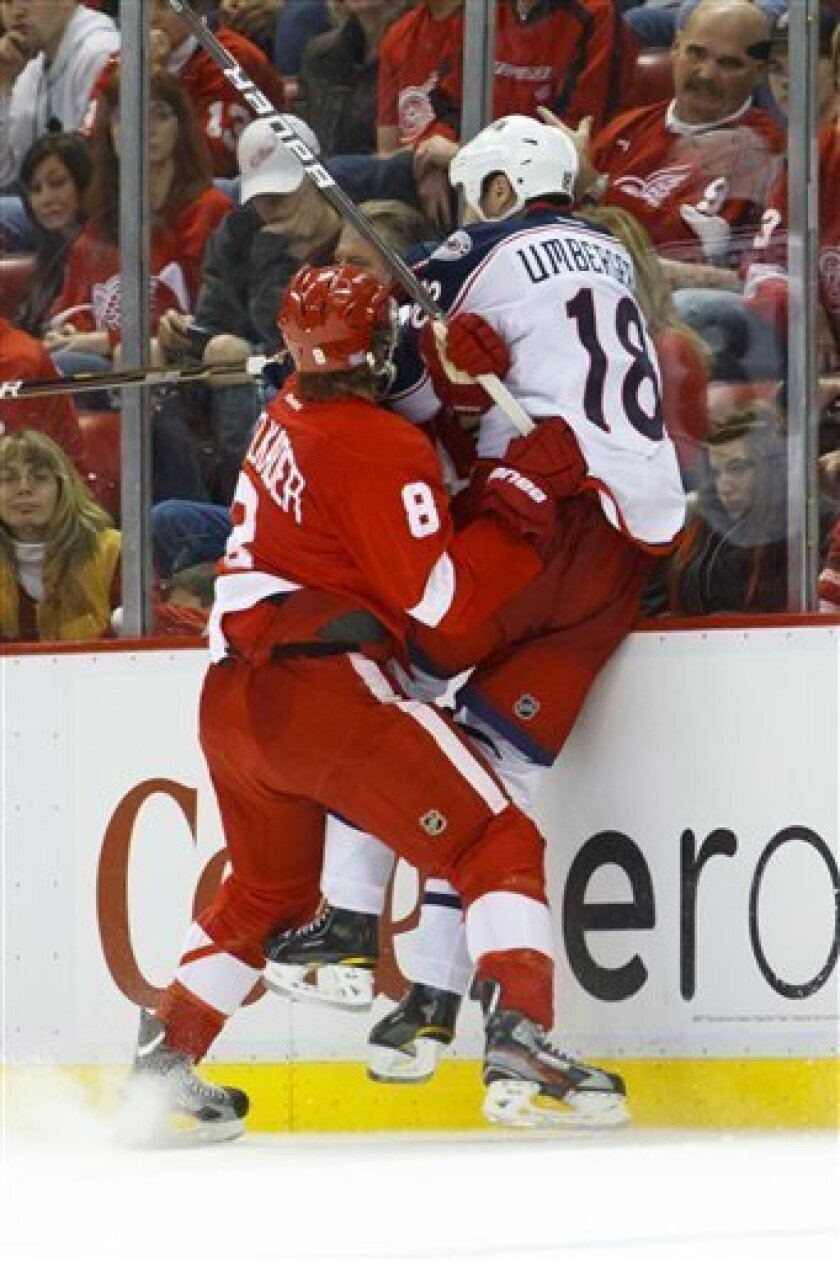 Detroit Red Wings left wing Justin Abdelkader (8) checks Columbus Blue Jackets left wing R.J. Umberger (18) into the boards during the third period of an NHL hockey game in Detroit, on Friday, Oct. 21, 2011. Detroit won 5-2. (AP Photo/Rick Osentoski)