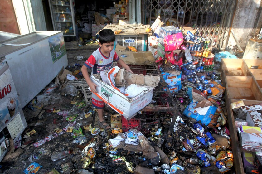 An Iraqi child helps his father (unseen) clean up his shop, which was destroyed the previous day in a car bomb attack in the Shiite-dominated district of Baghdad al-Jadida on Oct. 2, 2014.