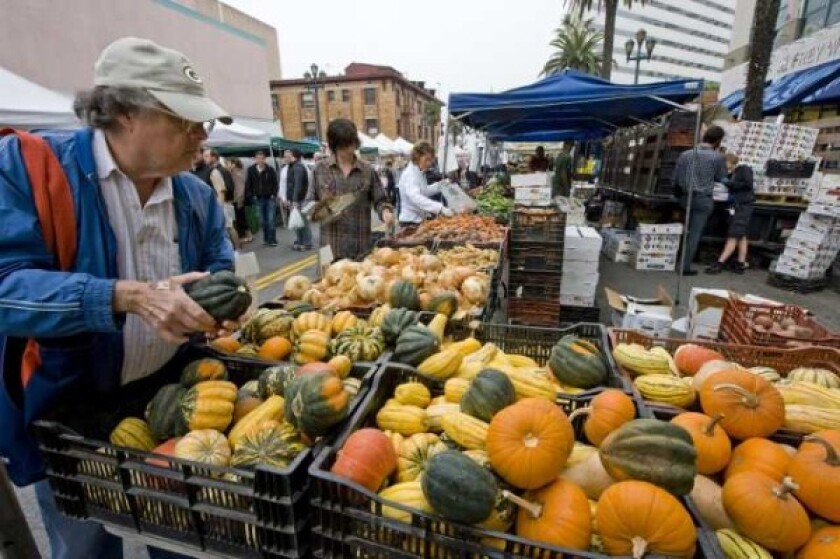 A customer browses among the squash and pumpkins grown by Tutti Frutti Farms in Lompoc at the Santa Monica farmers market. All weekend Santa Monica farmers markets will now be consolidated into a single Saturday market.