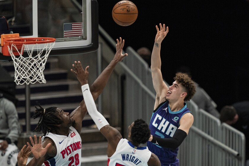 Charlotte Hornets guard LaMelo Ball, right, shoots the ball over Detroit Pistons center Isaiah Stewart, left, and guard Delon Wright during the first half of an NBA basketball game in Charlotte, N.C., Thursday, March 11, 2021. (AP Photo/Jacob Kupferman)