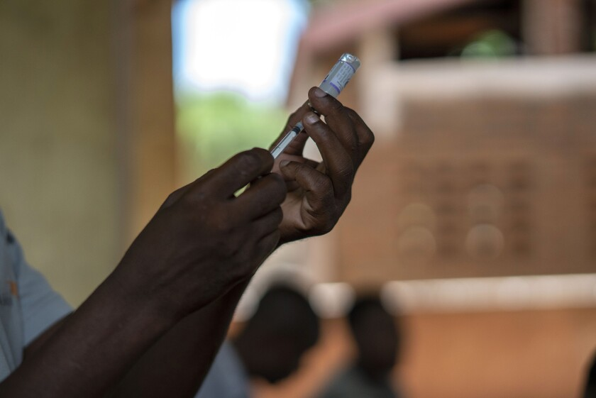 A health worker fills a syringe with vaccine.