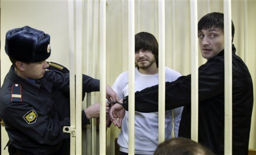 Brothers, Dzhabrail, center, and Ibragim Makhmudov, right, charged with the killing of Russian investigative reporter Anna Politkovskaya, seen before a trial in a military court in Moscow, Tuesday, Dec. 2, 2008. A lawyer says a man accused of killing Russian investigative reporter Anna Politkovskaya has offered to turn himself in if authorities promise him an open trial by jury. The three men being tried on murder charges include a former police officer and two Makhmudov's brothers. (AP Photo/Ivan Sekretarev)
