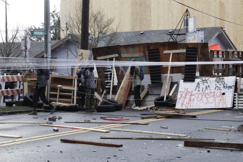 Protesters stand behind barricades at their encampment outside a home in Portland, Ore., on Wednesday, Dec. 9, 2020. Makeshift barricades erected by protesters are still up in Oregon's largest city a day after Portland police arrested about a dozen people in a clash over gentrification and the eviction of a family from a home. (AP Photo/Gillian Flaccus)