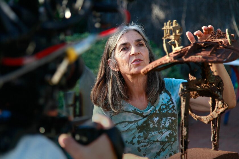 """Encinitas resident Jean Radakovich touches one of her family sculptures as she is filmed for a documentary about her parents, Svetozar """"Toza"""" Radakovich and Ruth Radakovich."""