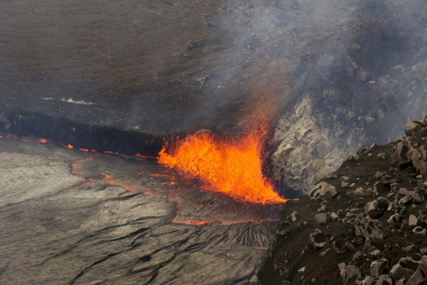 In this April 26, 2015 photo provided by U.S. Geological Survey Hawaiian Volcano Observatory, sparks rise from Kilauea volcano on Hawaii's Big Island. The public is getting their first look at the lake of lava on Hawaii's Kilauea volcano that has been rising over the past week and, at times, overfl