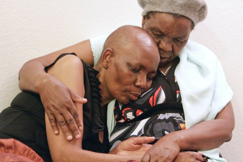 Tsitsi Mutseta, left, a local woman from Zimbabwe who is in stage 4 breast cancer, rests on her mother Lucia Mutseta, who had traveled from Zimbabwe to be with her ailing daughter, in La Mesa on May 17.