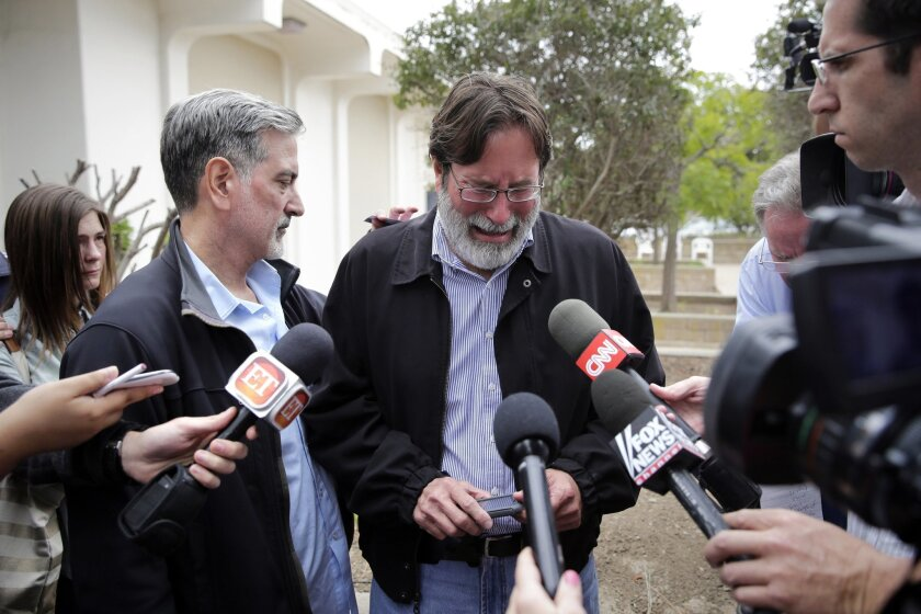FILE - In this May 24, 2014, file photo, Richard Martinez, center, who said his son Christopher Martinez was killed in a mass shooting that took place in Isla Vista, Calif., is comforted by his brother Alan as he talks to media outside the Santa Barbara County Sheriff's Headquarters in Santa Barbara, Calif. Martinez thinks of his son every day, says, and with those thoughts come the constant reminder of a young life cut tragically short by one of the nation's worst school killings. (AP Photo/Jae C. Hong, File)