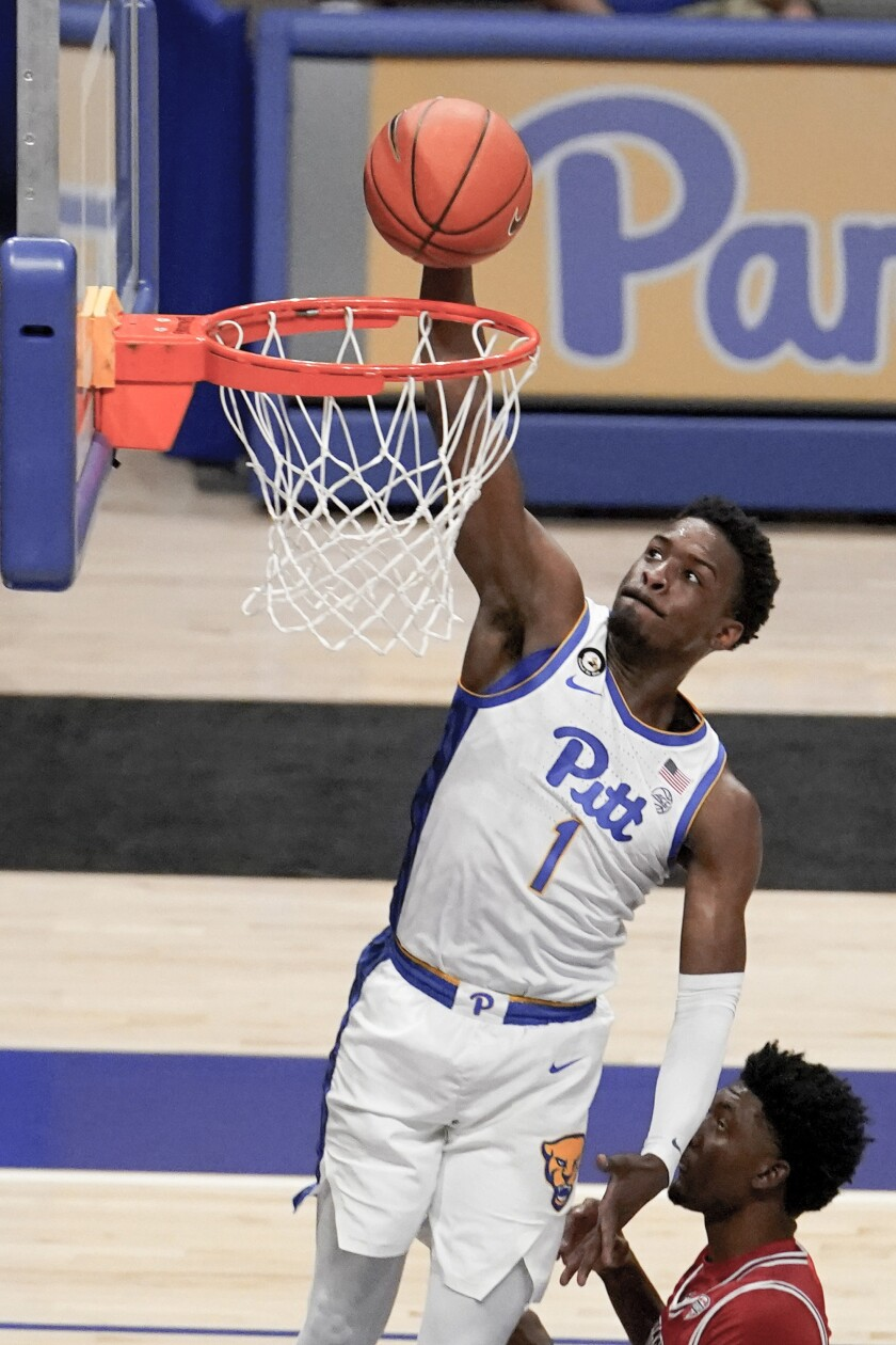 Pittsburgh's Xavier Johnson (1) dunks over Northern Illinois' Keenon Cole during the first half of an NCAA college basketball game Saturday, Dec. 5, 2020, in Pittsburgh. (AP Photo/Keith Srakocic)