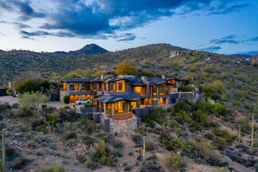 A photo of a two story mansion in a desert landscape