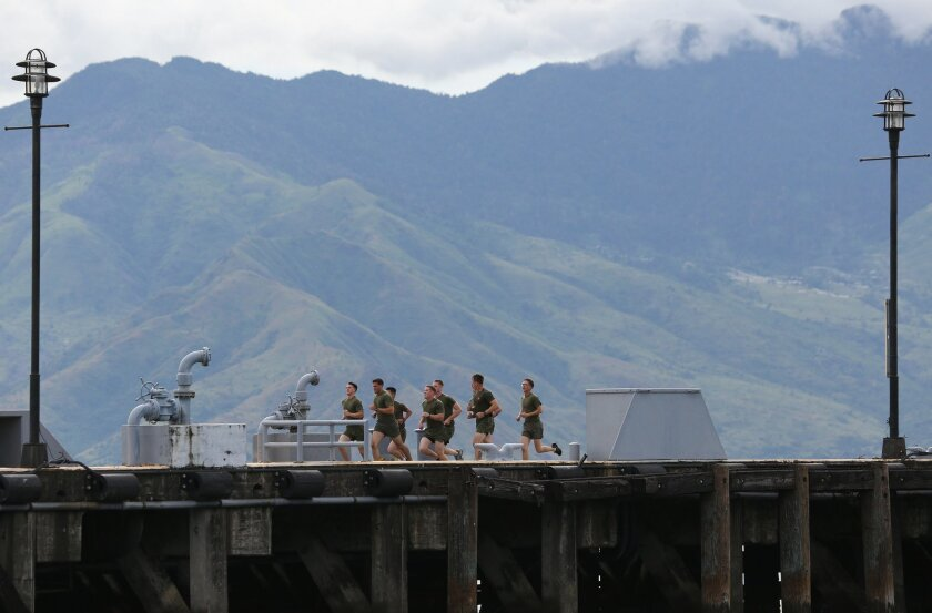 In this Saturday, Oct. 18, 2014 photo, U.S. Marines from the USS Peleliu jog around the pier at the Subic Bay free port in the Philippines. A Marine charged with murder in the killing of a transgender Filipino sparked public anger and revived debate over the U.S. military presence. The nations signed a new accord in 2014 that allows greater U.S. military access to Philippine military camps, part of Washington's pivot back to Asia to counter rising Chinese might. (AP Photo/Aaron Favila)