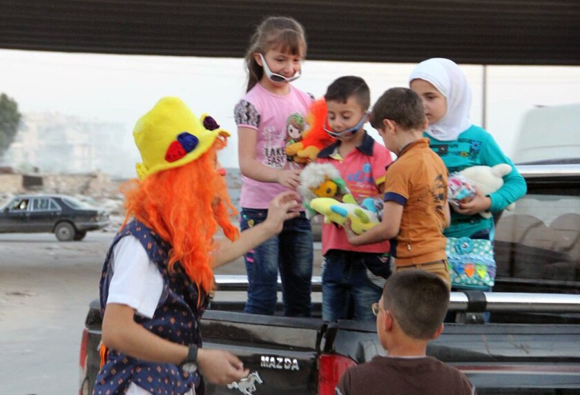 This undated photo courtesy of Ahmad al-Khatib, a media activist in Aleppo, shows Syrian social worker Anas al-Basha, 24, dressed as a clown, distributing toys to children in Aleppo, Syria.