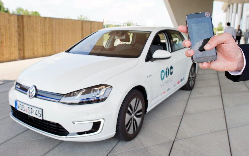 The driverless fleet is coming! In June, a man uses his smartphone to instruct a driverless Volkswagen E-Golf to look for a parking spot.