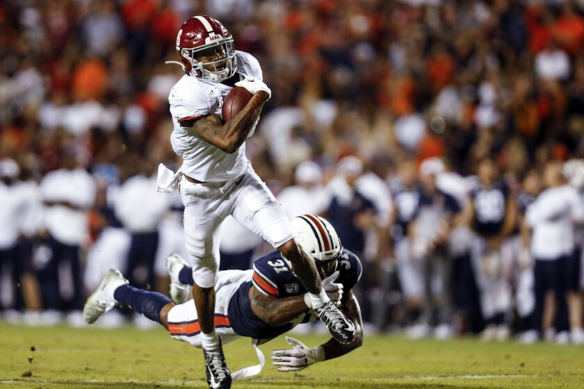 FILE - In this Nov. 30, 2019, file photo, Alabama wide receiver DeVonta Smith (6) catches a pass as Auburn linebacker Chandler Wooten (31) tries to tackle him during the second half of an NCAA college football game in Auburn, Ala. DeVonta Smith could be tearing up the NFL instead of the Southeastern Conference. The Alabama standout has 38 receptions for 483 yards and four touchdowns in four games. (AP Photo/Butch Dill, File)