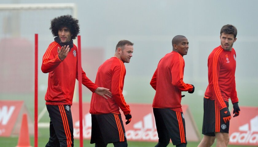 Manchester United's Marouane Fellaini , left, Wayne Rooney, second left, Ashley Young and Michael Carrick, right, attend a training session at the Aon Training Complex, Carrington, England, Monday Nov. 2, 2015. (Martin Rickett/PA via AP) UNITED KINGDOM OUT