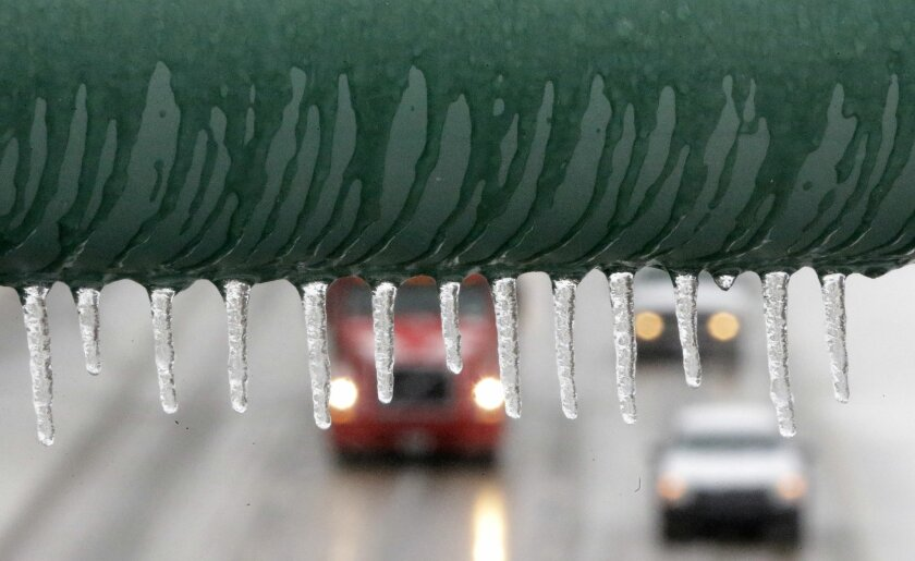 Traffic slowly moves along an ice covered highway Friday, Dec. 6, 2013, in Dallas. Winter storm and ice warnings are in effect through much of today for parts of six states in the Midwest, including Texas, Missouri, Illinois and Indiana. (AP Photo/LM Otero)