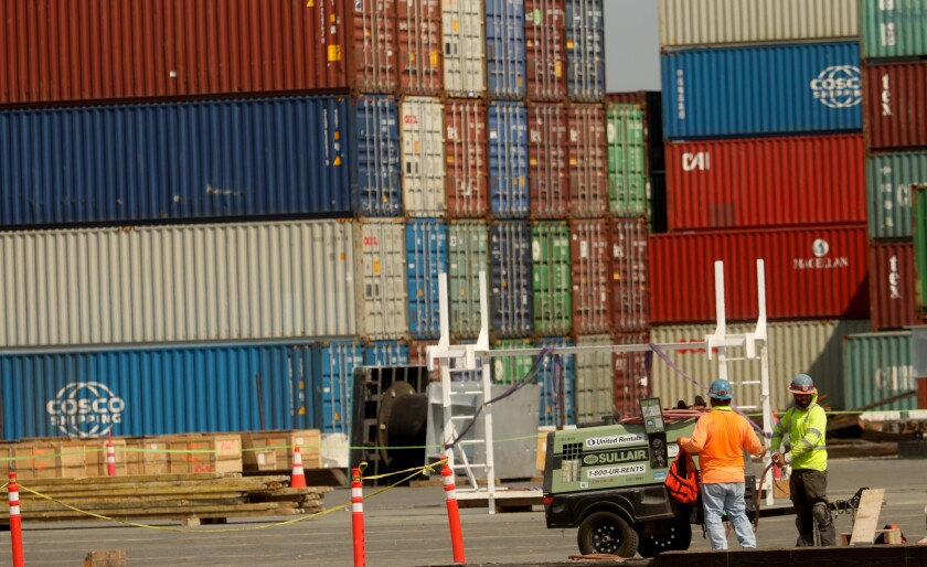 This photo shows men working with shipping containers in the background.