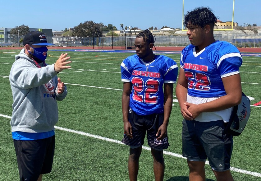 Crawford coach Matt Marquez talks with players Abdi Ali (center) and Kevin Luong at a recent Colts practice.