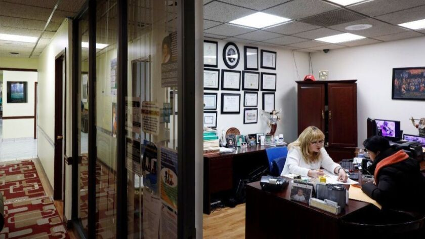 Sandra Wilson, left, a partner in Gladys R. Wilson and Associates, works with client Alba Torres on her taxes in her office March 4, 2019, on Chicago's Northwest Side.