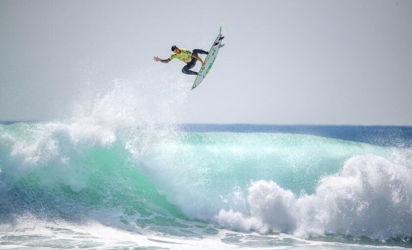 A surfer flies above a crashing blue wave