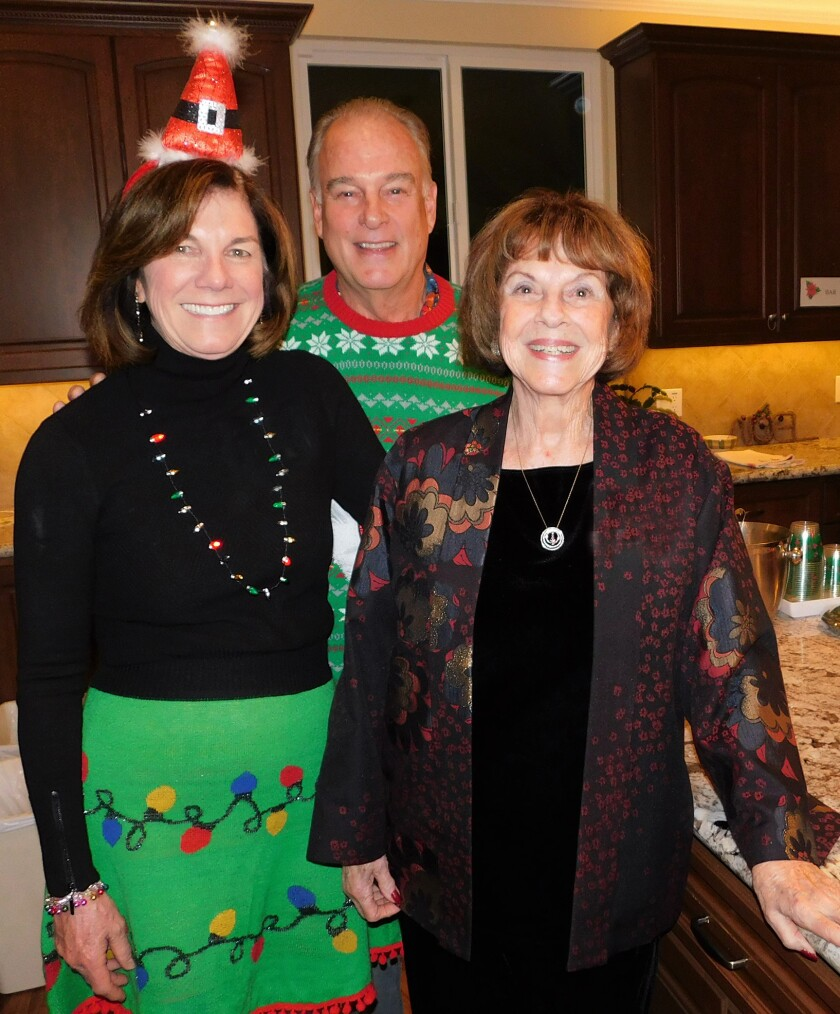 Terry and Woody Walker were the kitchen elves at the Kiwanis Club Christmas party held at the home of Ellie Wildermuth, right.